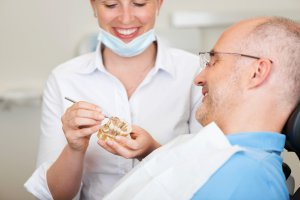 Smiling Female Dentist Explaining Artificial Teeth