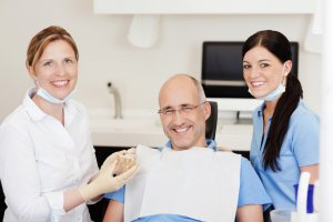 Dentist With Teeth Model And Male Patient