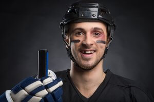 Funny hockey player smiling with one tooth missing. Isolated on